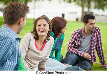 Casual laughing students sitting on the grass chatting on...
