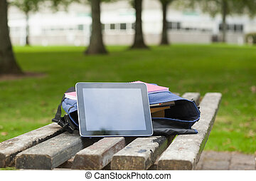 Purple schoolbag and tablet lying on park bench on campus at...