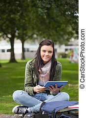 Smiling brunette student using tablet sitting on bench on...