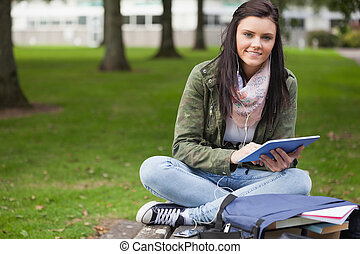 Happy brunette student using tablet sitting on bench on...