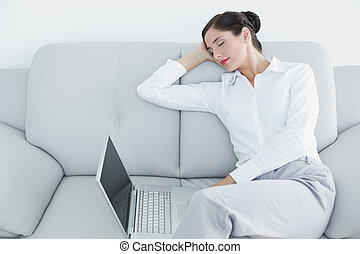 Well dressed woman resting while using laptop at home - Well...