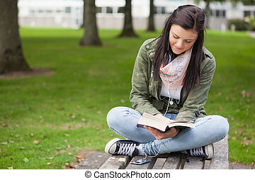 Happy brunette student sitting on bench reading on campus at...