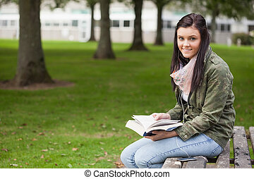 Cheerful brunette student sitting on bench reading on campus...