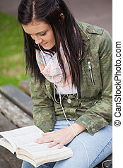 Content brunette student sitting on bench reading on campus...