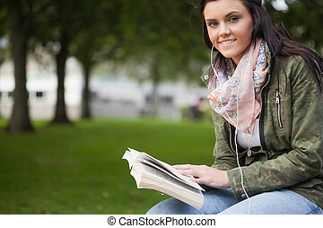 Gleeful brunette student sitting on bench reading on campus...