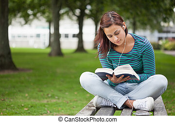 Content casual student sitting on bench reading on campus at...
