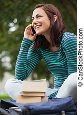 Cheerful casual student sitting on bench phoning on campus...