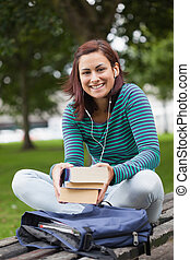 Cheerful casual student sitting on bench holding books on...