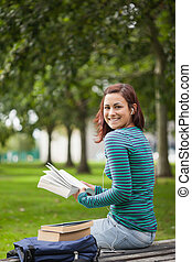 Happy casual student sitting on bench reading on campus at...