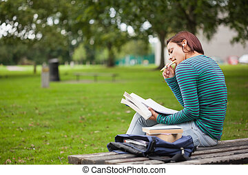 Thoughtful casual student sitting on bench reading on campus...