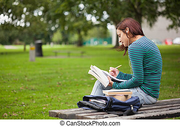 Serious casual student sitting on bench taking notes on...