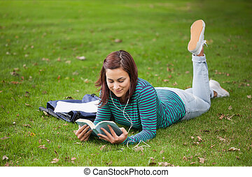 Content casual student lying on grass reading on campus at...