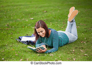Happy casual student lying on grass reading on campus at...