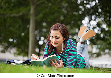 Calm casual student lying on grass reading on campus at...