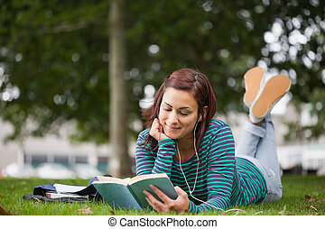 Smiling casual student lying on grass reading on campus at...