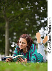 Attractive casual student lying on grass reading on campus...