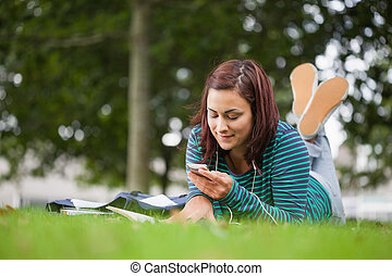 Attractive casual student lying on grass texting on campus...