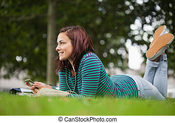 Smiling casual student lying on grass looking away on campus...