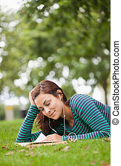 Casual student lying on grass read - Casual student lying on...