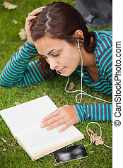 Calm casual student lying on grass reading a book on campus...