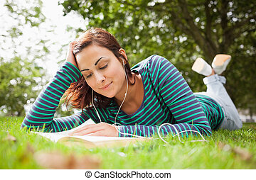 Smiling casual student lying on grass reading a book on...