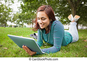 Happy casual student lying on grass using tablet on campus...