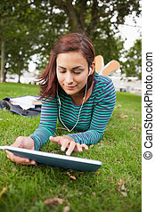 Calm casual student lying on grass using tablet on campus at...