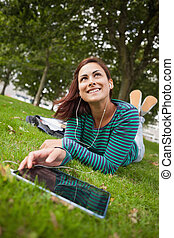 Day dreaming casual student lying on grass using tablet on...