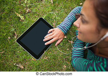 Casual student lying on grass using tablet listening to...