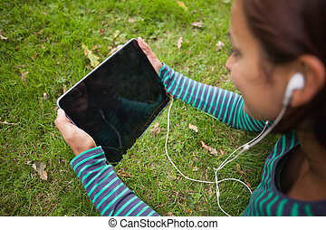 Casual student lying on grass holding tablet on campus at...