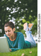 Content casual student lying on grass using laptop on campus...