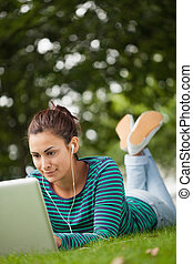 Happy casual student lying on grass using laptop on campus...