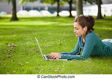 Calm casual student lying on grass using laptop on campus at...