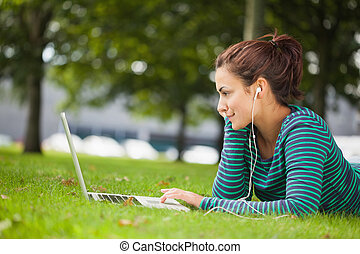 Attractive casual student lying on grass using laptop on...