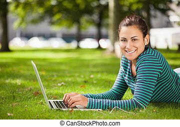 Attractive casual student lying on grass using laptop...