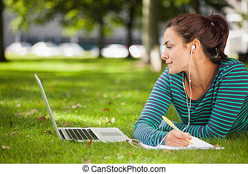 Attractive casual student lying on grass taking notes on...