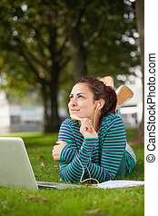 Thoughtful casual student lying on grass taking notes on...