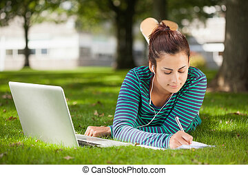 Calm casual student lying on grass taking notes on campus at...