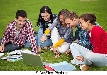 Five students sitting on the grass - Five students sitting...