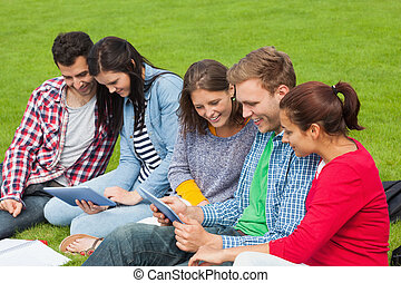 Five students sitting on the grass using tablet on campus at...