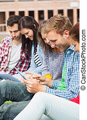 Five casual students sitting on the grass using tablet on...