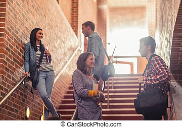 Casual students standing on stairs chatting in college