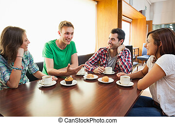 Four casual students having a cup of coffee chatting