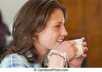 Pretty smiling student drinking a cup of coffee