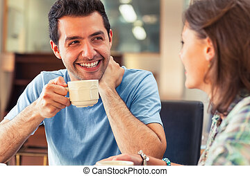 Two laughing students having a cup of coffee in college...