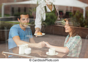 A couple holding hands while waitress serving food in...
