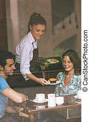 Smiling waitress serving food to a couple in college canteen
