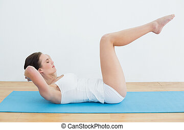 Side view of a woman doing stomach crunches on exercise mat...