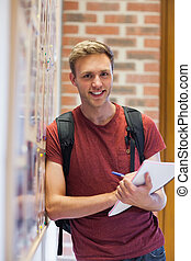 Handsome smiling student taking notes next to notice board