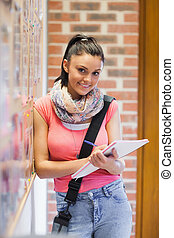 Pretty smiling student taking notes next to notice board